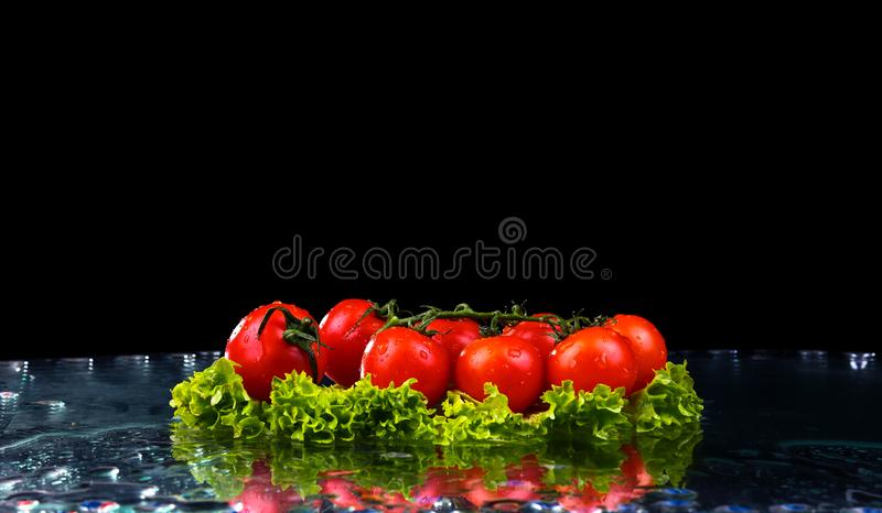 Fresh tomato cherry and green fresh salad with water drop splash on dark background Macro drops of water fall on the red cherry royalty free stock photo