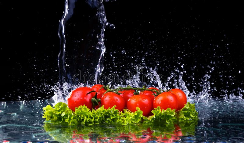 Fresh tomato cherry and green fresh salad with water drop splash on dark background Macro drops of water royalty free stock photos