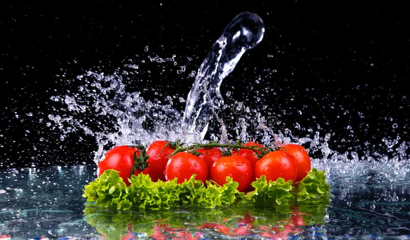 Fresh tomato cherry and green fresh salad with water drop splash on dark background Macro drops of water fall on the red cherry royalty free stock image