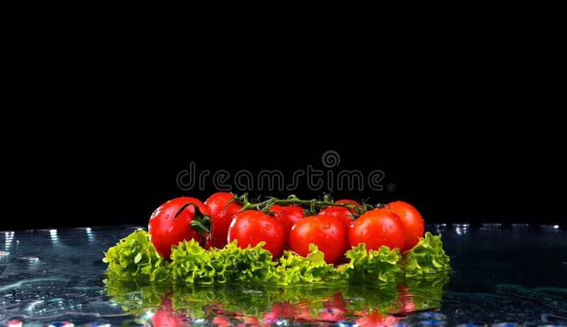 Fresh tomato cherry and green fresh salad with water drop splash on dark background Macro drops of water fall on the red cherry royalty free stock photos