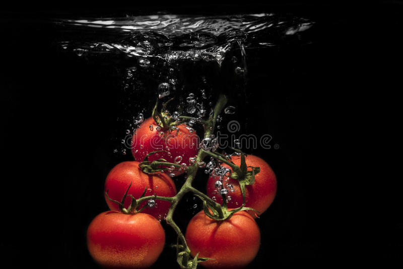 Fresh tomato dropped into water stock photo
