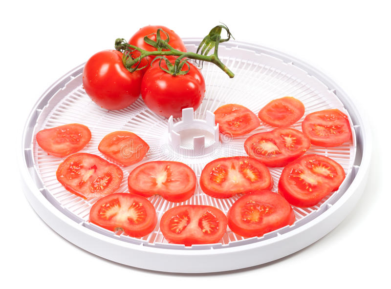 Fresh tomato prepared to dehydrated. On food dehydrator tray royalty free stock image
