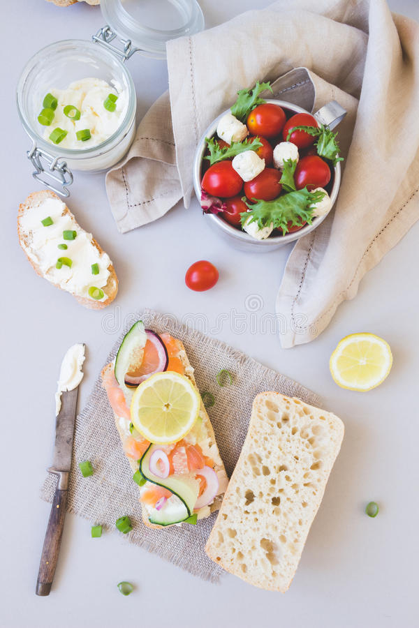 Fresh tomato salad and ciabatta bread with cream cheese and salmon on the gray background stock image