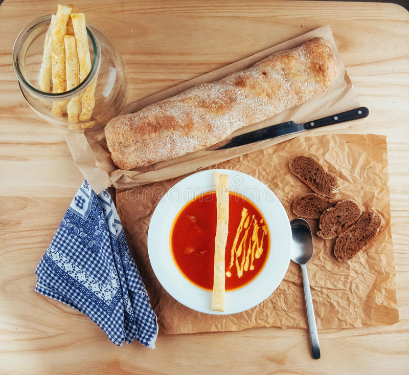 Fresh tomato soup in a white mask with bread baguette.  stock images