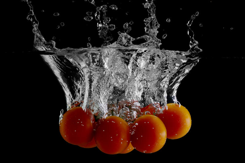 Fresh tomatoes. Falling into water royalty free stock image