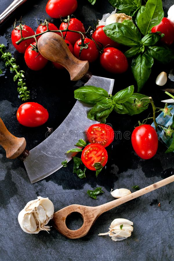 Fresh tomatoes with basil garlic and sea salt on black slate background stock photos