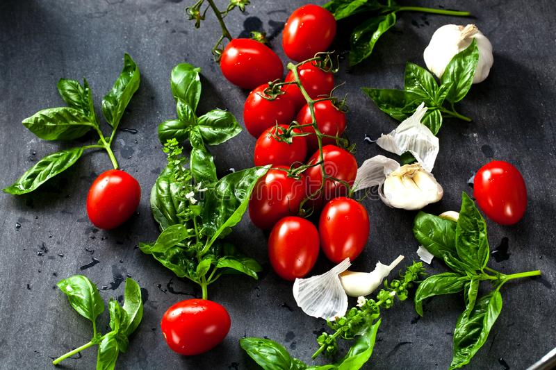 Fresh tomatoes with basil garlic and sea salt on black slate background stock images
