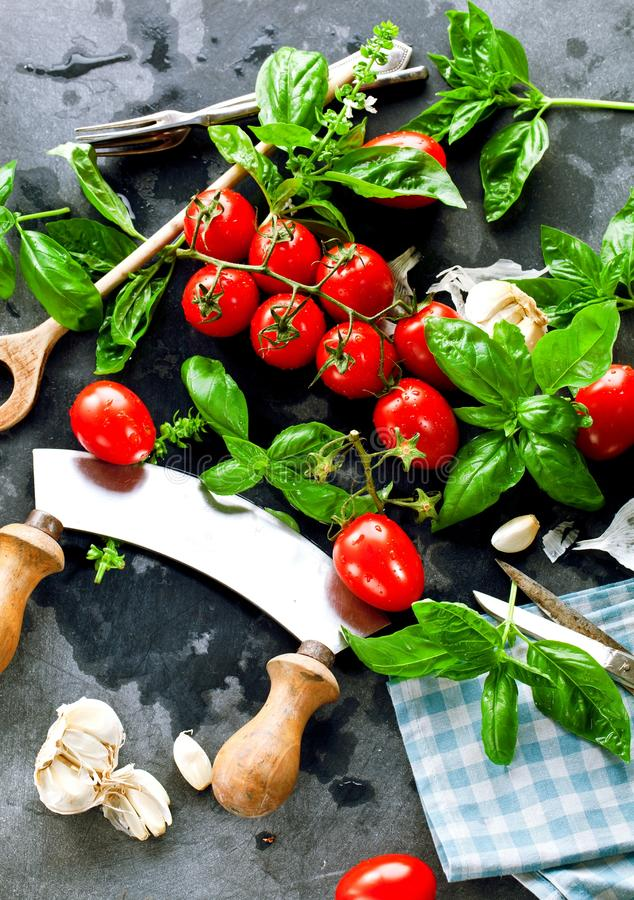 Fresh tomatoes with basil garlic and sea salt on black slate background royalty free stock image