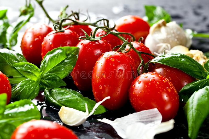 Fresh tomatoes with basil garlic and sea salt on black slate background stock photo