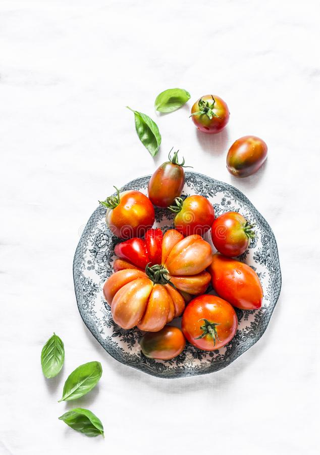 Fresh tomatoes and basil leaves on a light background, top view royalty free stock images