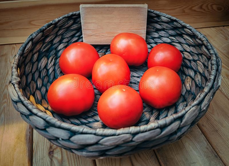 Fresh tomatoes in a basket on wooden background with empty space royalty free stock photography
