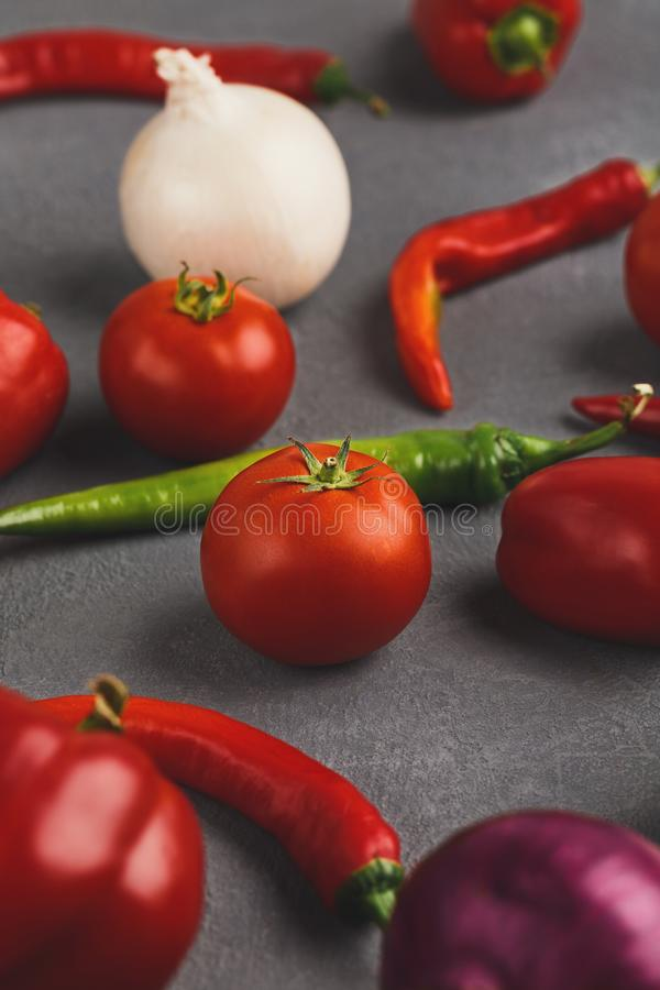 Fresh tomatoes and chilli closeup on grey rustic wood. Fresh organic vegetables on wood background. Cherry tomatoes, variety of chilli and onion, bell pepper on stock photos