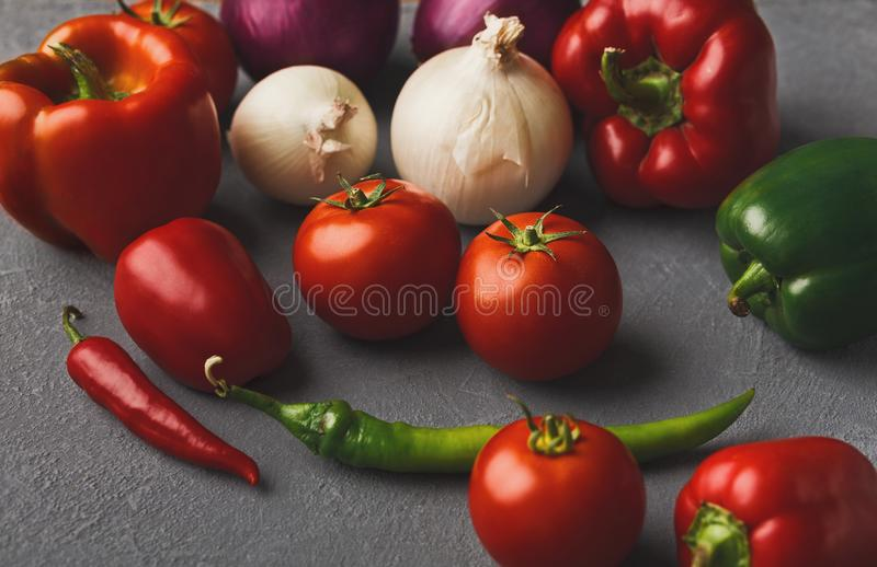 Fresh tomatoes and chilli closeup on grey rustic wood. Fresh organic vegetables on wood background. Cherry tomatoes, variety of chilli and onion, bell pepper on stock photo