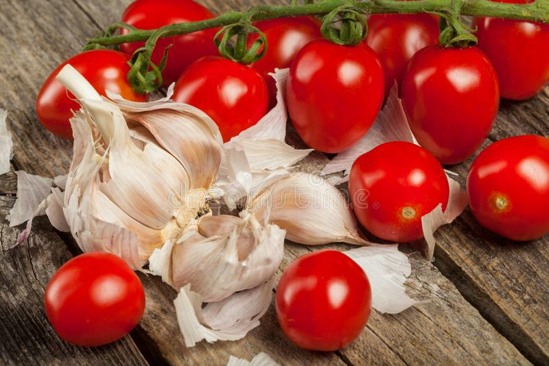 Tomatoes and garlic. Fresh tomatoes and gloves of garlic on the wood royalty free stock photo