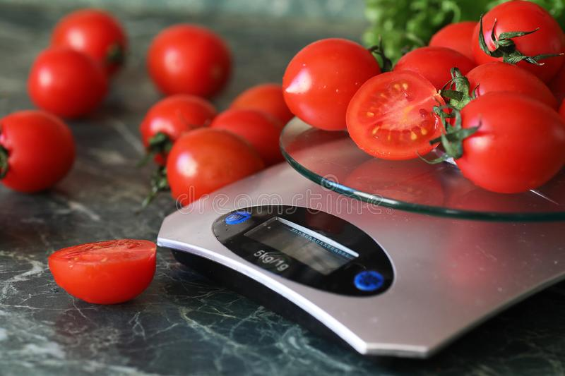 Fresh tomatoes on kitchen scales weighing. And measuringr royalty free stock photos