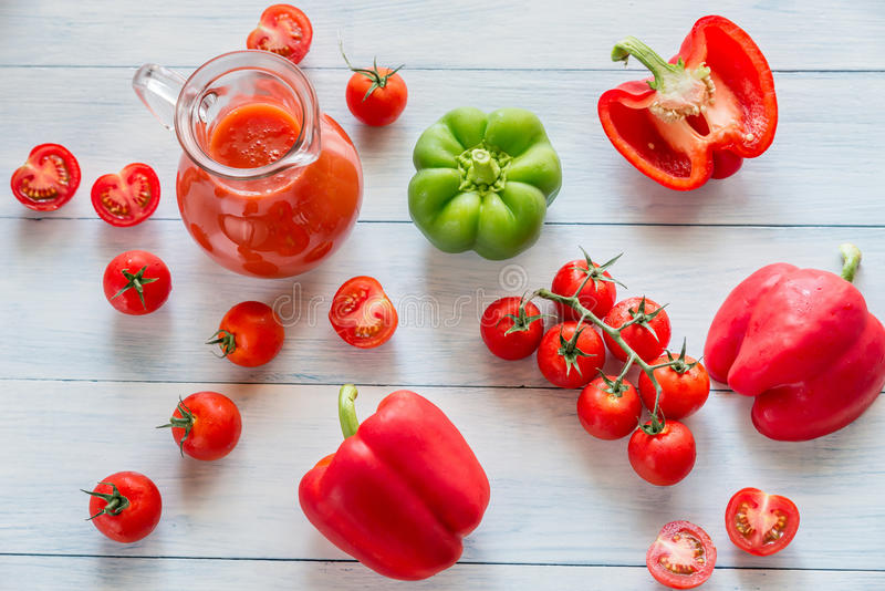 Fresh tomatoes, peppers and jug of juice stock photo
