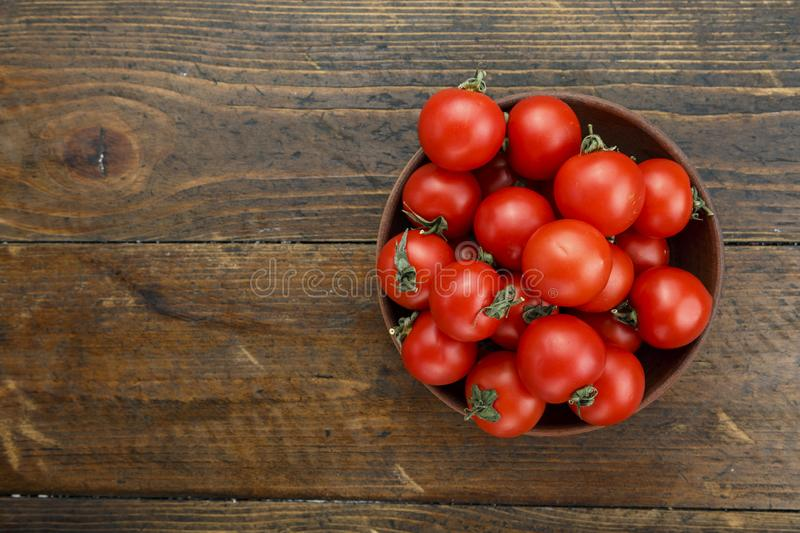 Fresh tomatoes in a plate on a wooden background. Harvesting tomatoes. Top view royalty free stock photography
