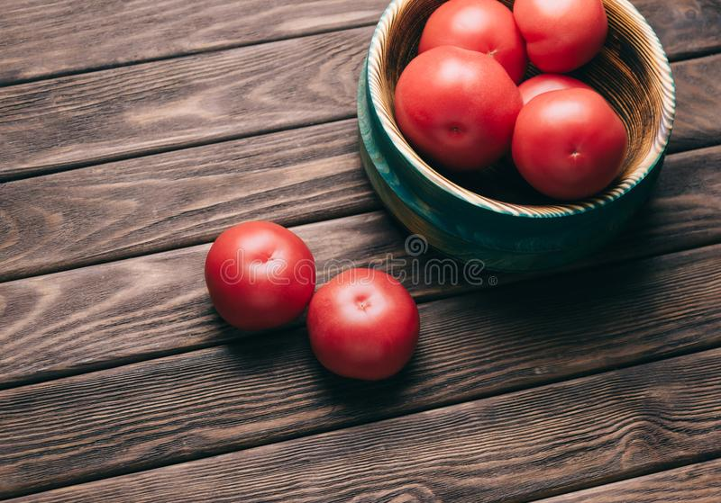 Fresh tomatoes in a wooden bowl. stock photos