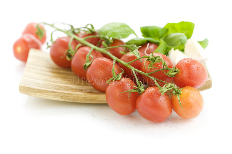Fresh tomatoes on wooden plate stock photo