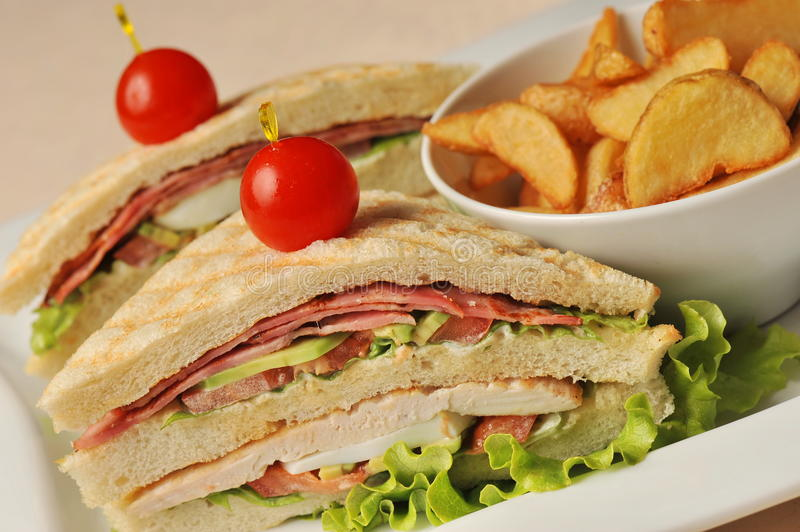Fresh triple decker hotel club sandwich. With french fries on side royalty free stock image