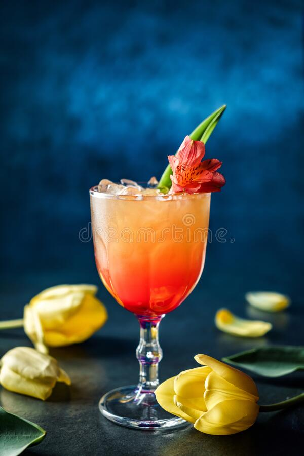Free Fresh Tropical Cocktail With Ice And Flowers In Wineglass On Dark Blue Background. Summer Cold Drink And Cocktail Stock Image - 183876751