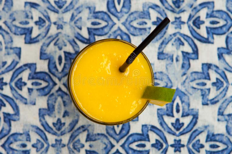 Fresh tropical fruit smoothie mango juice on blue background. Top view. stock photography