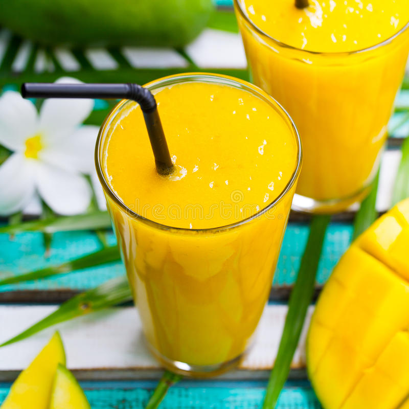 Fresh tropical fruit smoothie mango juice. Fresh tropical fruit smoothie mango juice and fresh mango on a outdoor tropical background stock photos