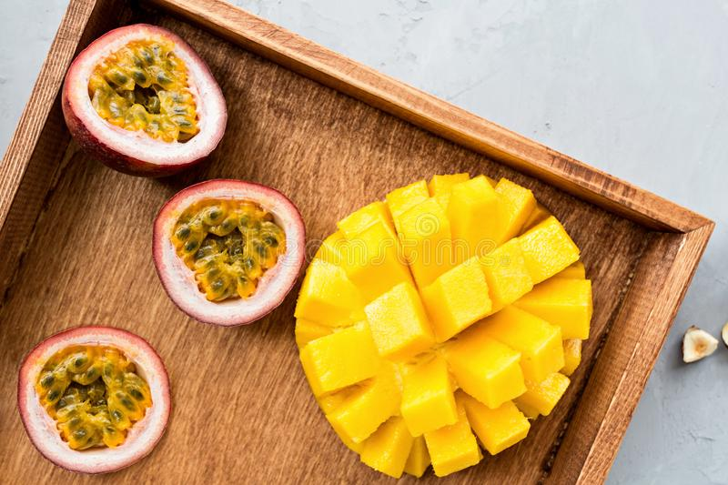 Fresh tropical fruits: mango and passion fruit on wooden background. Flatlay, top view, overhead. Healthy lifestyle and summer royalty free stock photography