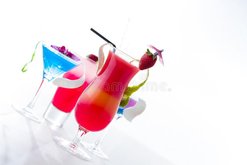 Fresh tropical layered cocktails over white. Background royalty free stock image