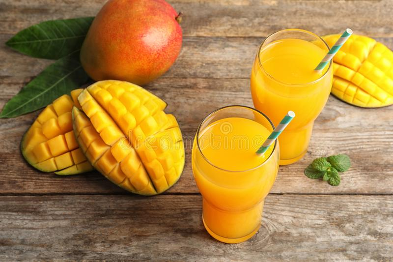 Fresh tropical mango juice and fruits. On wooden table stock photo