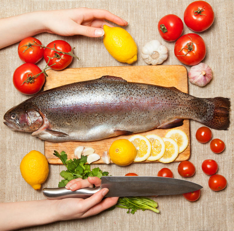 Fresh trout with vegetables on cutting board. stock photography