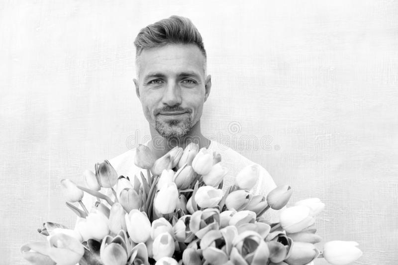 Fresh tulips. Giving her all best. Valentines day and anniversary. How to be romantic. Romantic gentleman. Man mature. Confident macho with romantic gift stock photo