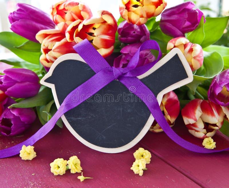 Fresh tulips and a little chalkboard. Fresh colorful tulips and a little chalkboard with copy space stock photo
