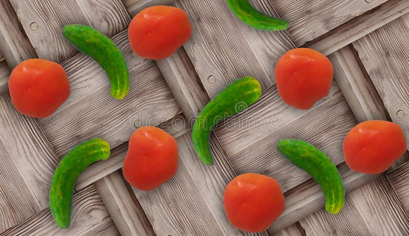 Fresh ugly croocked green cucumbers and fresh red tomatoes on wooden background royalty free stock photography