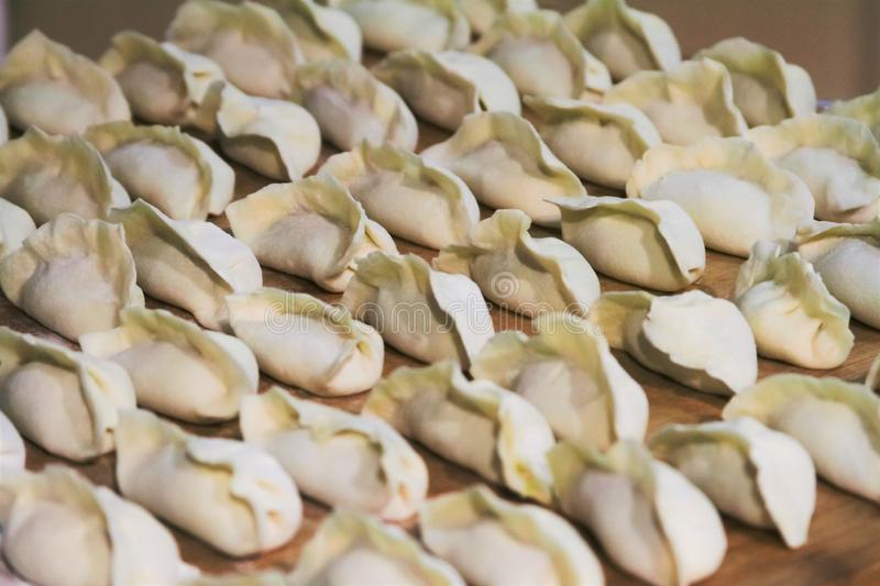 Fresh uncooked Chinese dumplings on cutting board royalty free stock images