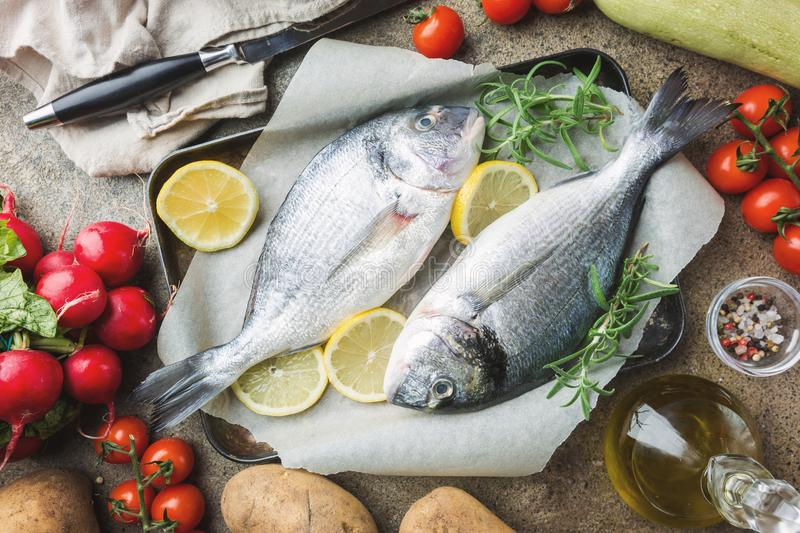 Fresh uncooked dorado. Or sea bream fish with ingredients, lemon and rosemary on paper over background, top view royalty free stock image