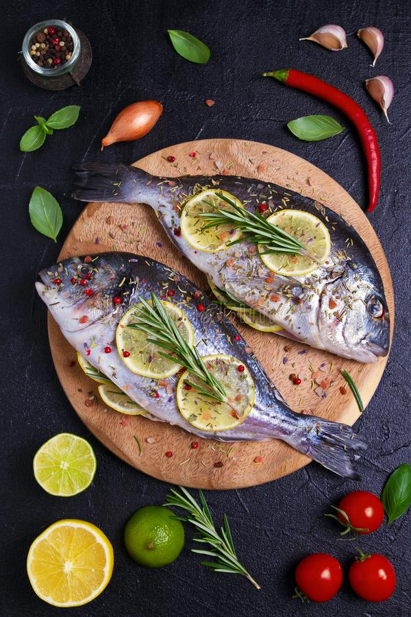 Fresh uncooked dorado or sea bream fish with lemon, herbs, vegetables and spices on black background. View from above, top royalty free stock images