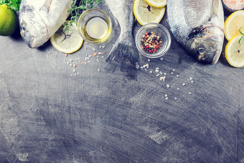 Fresh uncooked dorado. Or sea bream fish with lemon slices, spices and herbs. Mediterranean cuisine. Top view stock photos