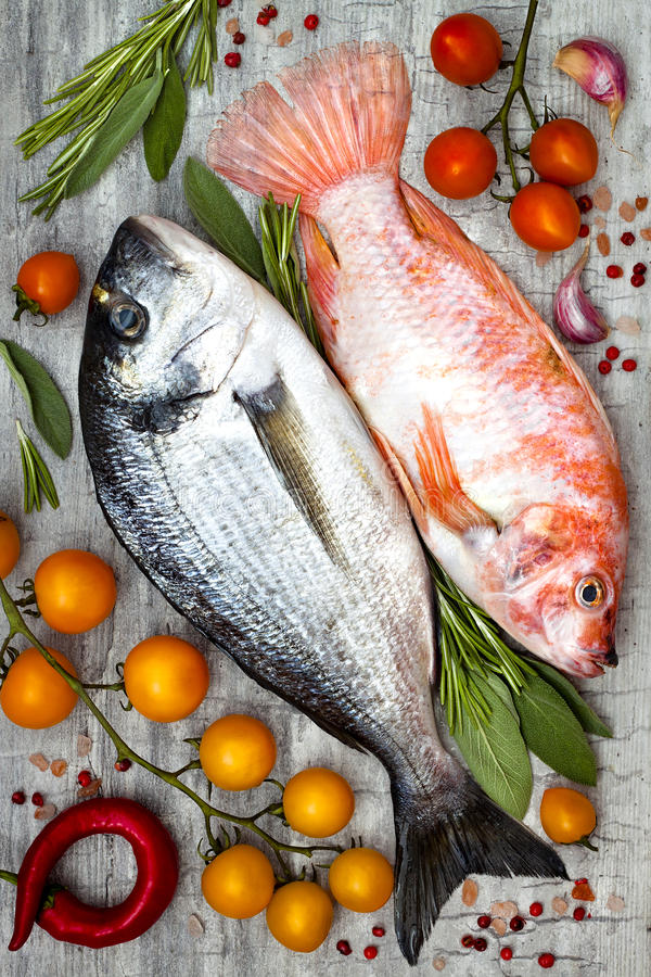 Fresh uncooked dorado or sea bream and red tilapia fish with lemon, aromatic herbs, vegetables and spices over grey background. Fresh uncooked dorado or sea stock photo