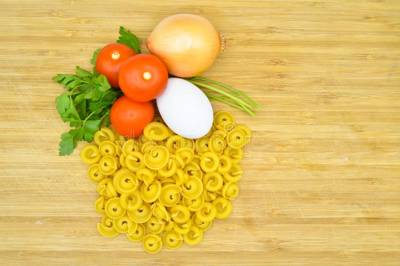 Fresh uncooked gold colored pasta, tomatoes, egg, parsley and onion. Isolated on cutting board stock image