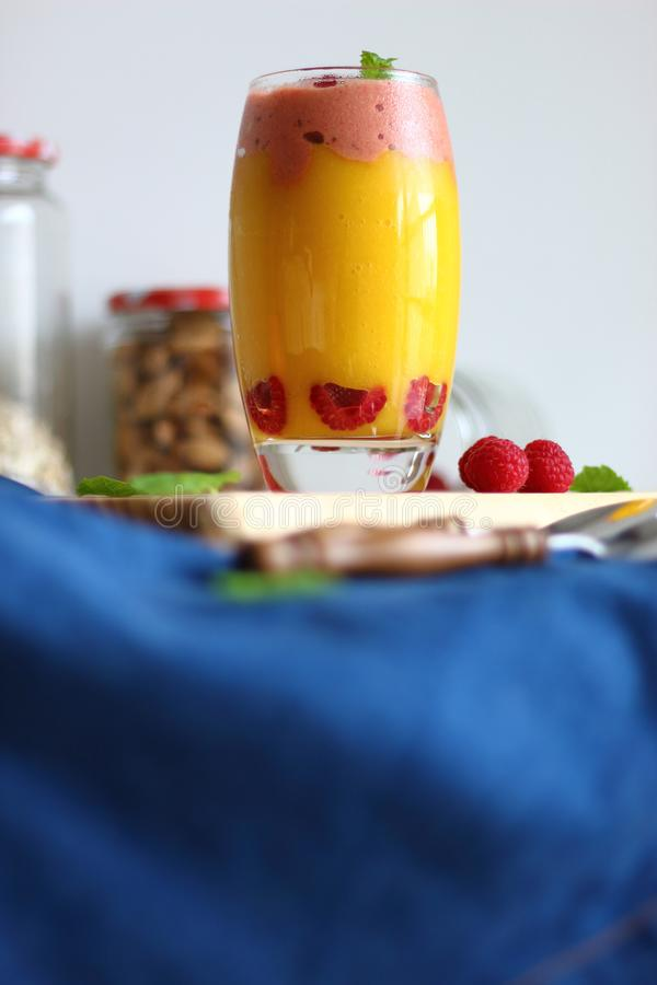 Fresh vegan layered dessert in a glass of colored smoothies of mango and banana with raspberries ice cream. stock image