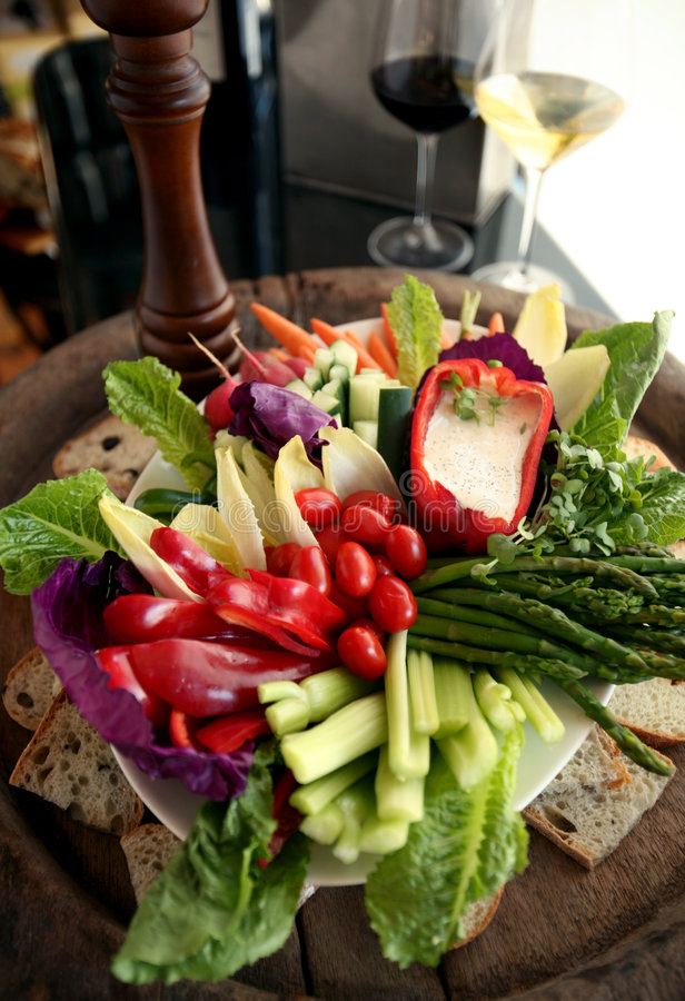 Fresh vegetable crudite platter. Vegetable platter with tomatoes, asparagus, celery sticks, red peppers and baguette royalty free stock photography