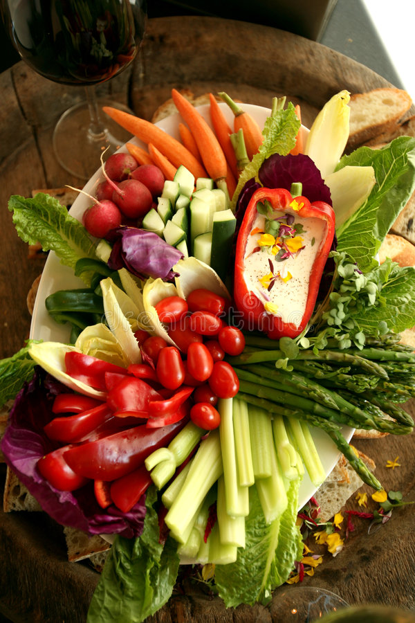 Fresh vegetable crudite platter. Vegetable platter with tomatoes, asparagus, celery sticks, red peppers and baguette royalty free stock photos