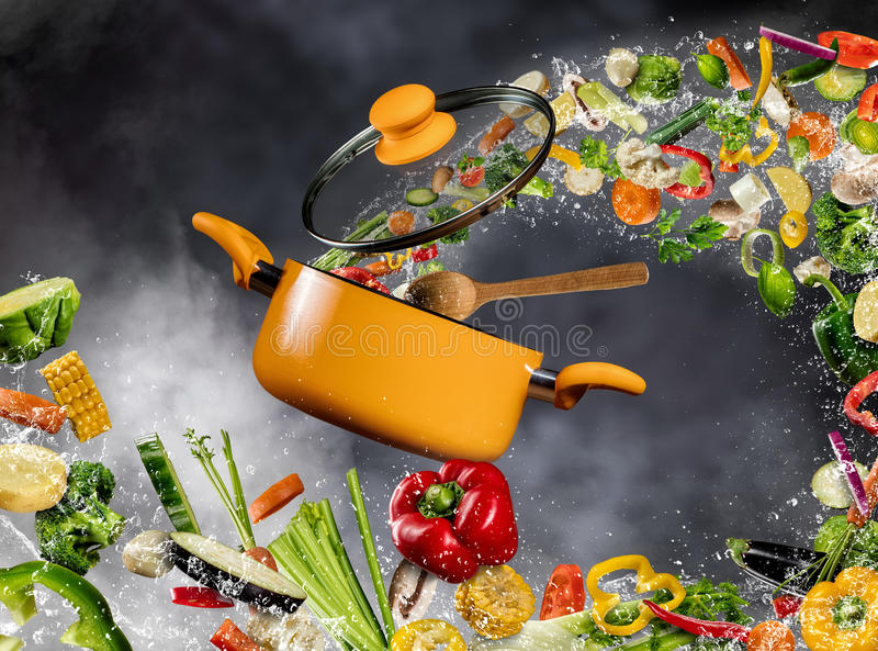 Fresh vegetable flying into a pot on dark background stock photography