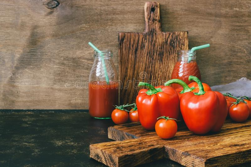 Fresh vegetable red peppers and cherry tomatoes, tomato juice on wooden table, rustic style. Selective focus. stock photo