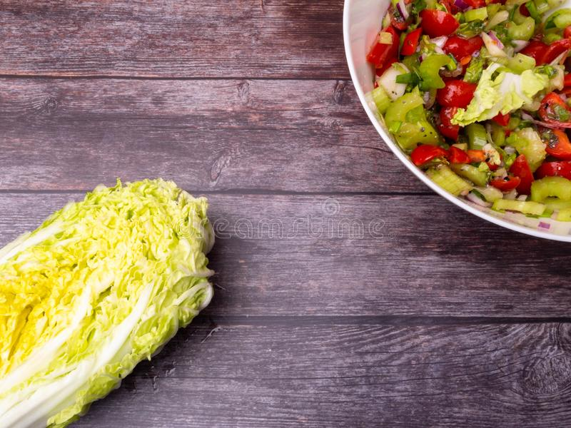 Fresh vegetable salad of chinese cabbage, tomato, pepper and onion with olive or sunflower oil on wooden table. Healthy food stock photos