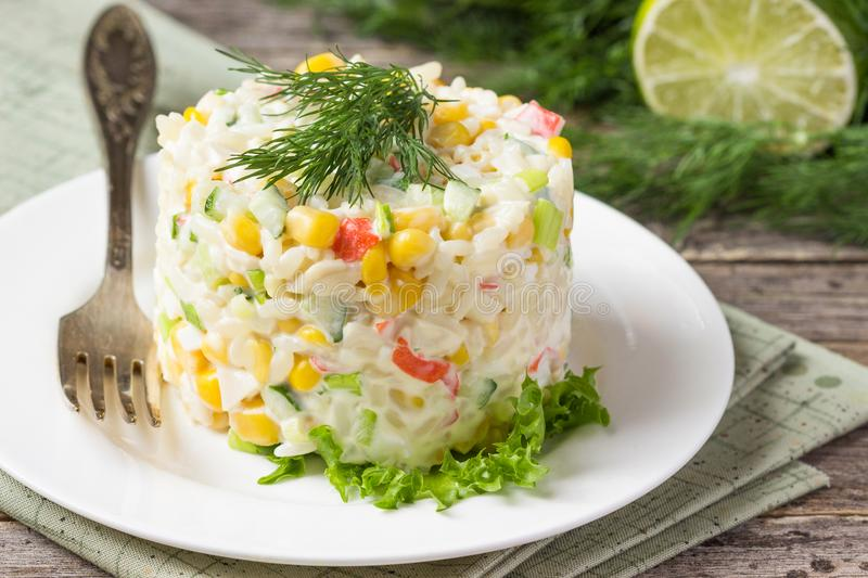 Fresh vegetable salad with corn, pepper, crab, cucumber, eggs and mayonnaise on the plate. stock photo