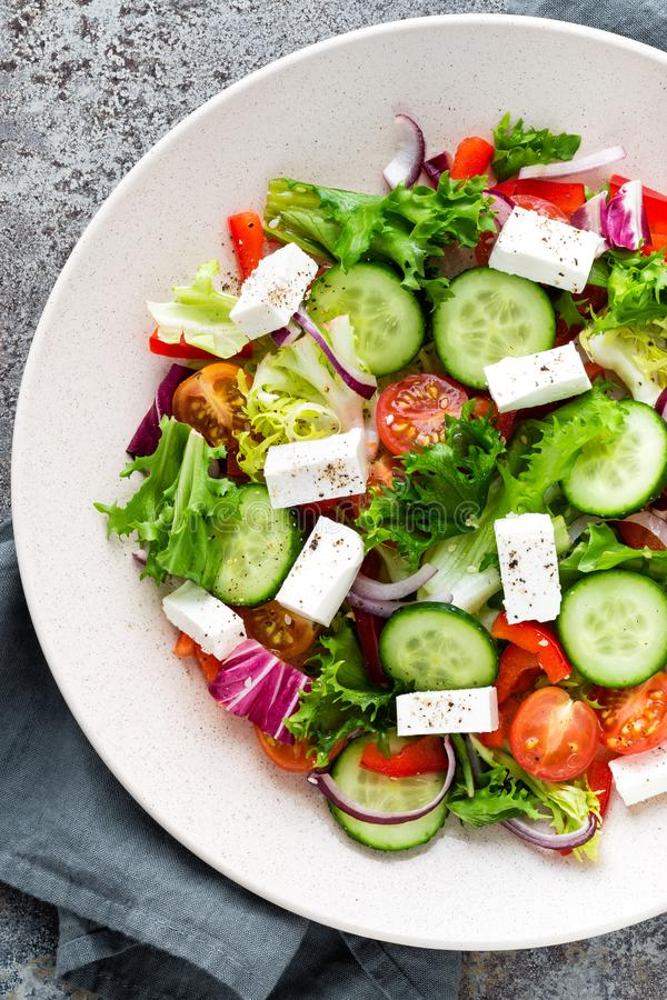 Fresh vegetable salad with feta cheese, fresh lettuce, cherry tomatoes, red onion and pepper. Top view stock photos