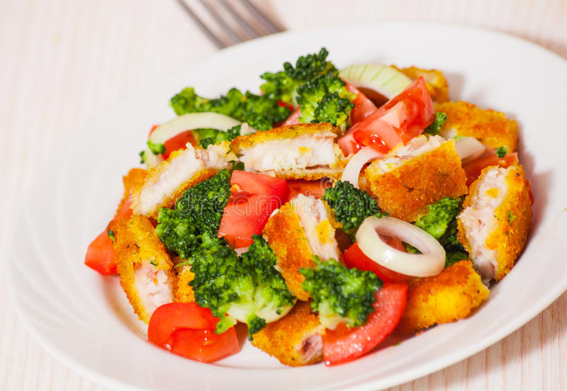 Fresh vegetable salad with fried breaded fish fillets for What vegetables go with fish