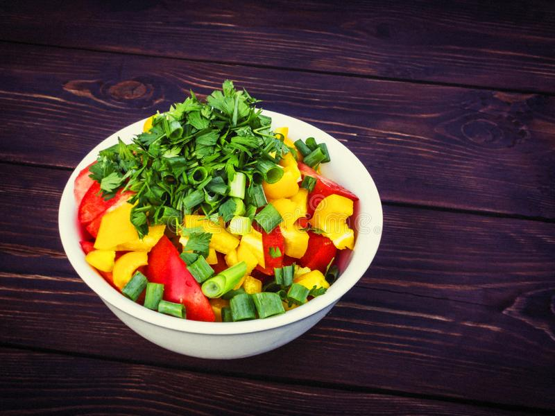 Fresh vegetable salad with herbs in a white bowl on a dark wooden table stock photo